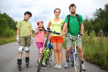 Active rest of family with roller skates and a bicycles