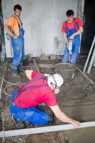 workers in construction room prepare mixture and pouringl floor