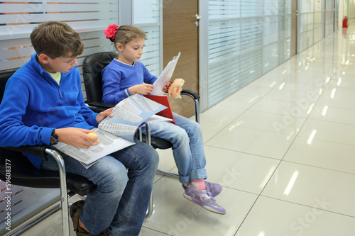 Boy and girl in jackets sitting on chairs in hallway