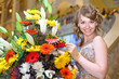 smiling girl in elegant dress next to bouquet of flowers