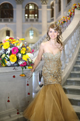 Beautiful girl in elegant dress next to bouquet of flowers