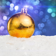 Golden Christmas ball on snow on blue festive background