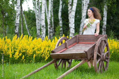 Young girl with old wooden cart on the field with green grass