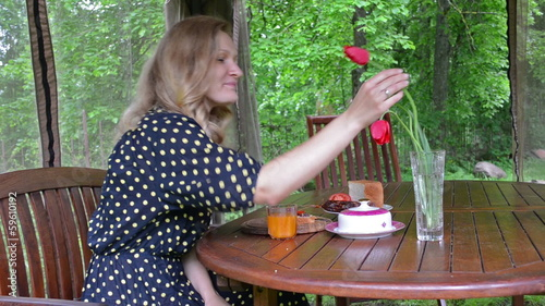 Woman in spotted dress smell red tulip flowers in vase and smile