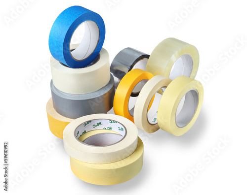 Several rolls of adhesive tapes different colors, sizes.
