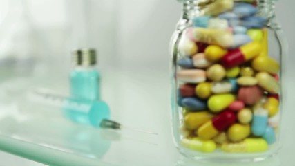 Syringe or Bottle of Pills Medical Choice Concept