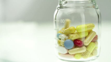 Glass Bottle Filling up with colorful pills
