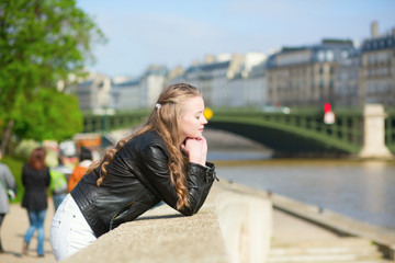 Thoughtful Parisian girl at the Seine embankment