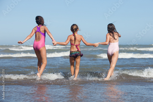 three happy girls running into the ocean