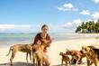 Junge Frau mit Strandhunden in der Karibik
