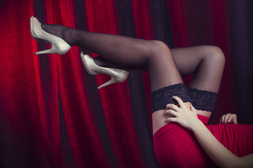 Woman's stockinged legs over cabaret red background