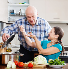 mature couple cooking food with vegetables