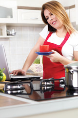 modern young housewife using a laptop while cooking