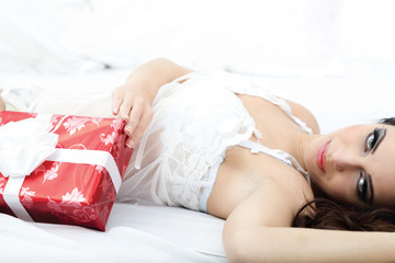 sexy woman in white lingerie lying on a bed with red gift