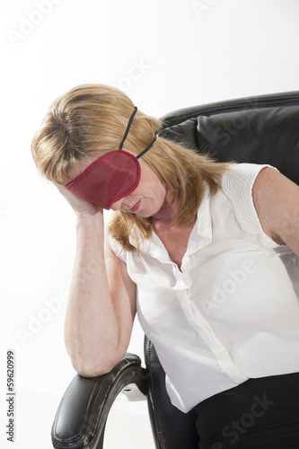 Woman wearing eyemask sleeping in an office chair