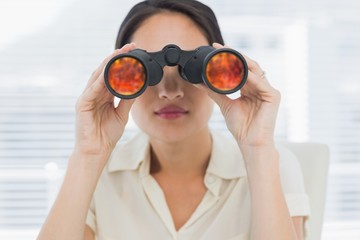 Close-up of a businesswoman looking through binoculars