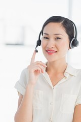 Beautiful smiling female executive with headset