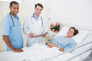 Doctor and surgeon visiting patient in hospital