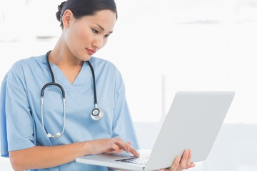 Concentrated surgeon using a laptop in hospital