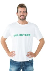 Portrait of a happy male volunteer standing with hands on hips