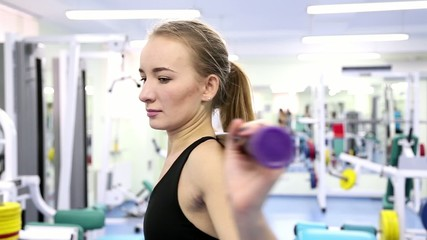 Young woman trains at a gym (exercise with a stick)