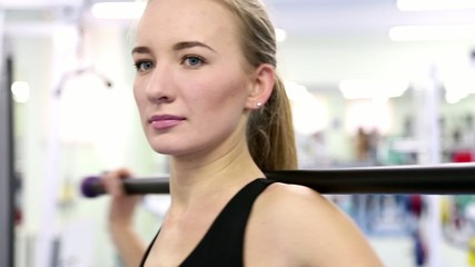 Young woman trains at a gym (exercise with a stick) close-up