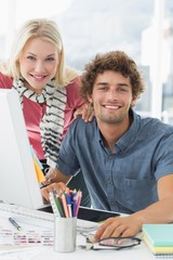 Smiling casual couple using computer in bright office
