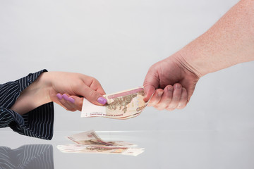 Female and male hands hold banknotes
