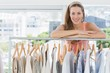 Female fashion designer with rack of clothes in store