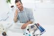 Fashion designer using laptop and phone in studio