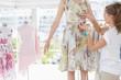 Fashion designer measuring model's waist