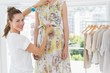 Portrait of a female fashion designer measuring model