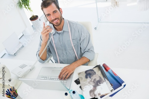 Fashion designer using laptop and phone in studio