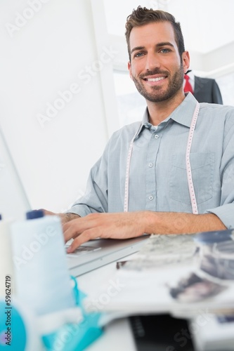 Smiling young male fashion designer using laptop