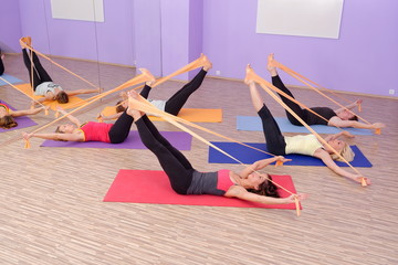 Aerobics HOT pilates group with rubber bands in a row