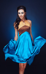Elegant asian girl in fluttering blue dress