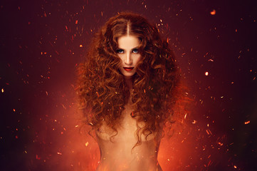 Fantasy fire lady. Red hair over fire sparkles.