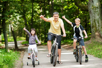 Happy family in the park on bicycles