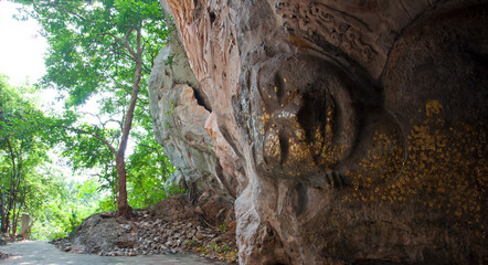 The stucco of ancient reclining Buddha at the Khao Ngu Cave in T