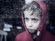 Sad boy looking through window to the rain