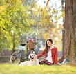 Beautiful female sitting on a green grass with her dog in a park