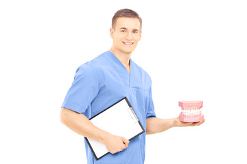 Male dentist surgeon holding dentures and clipboard