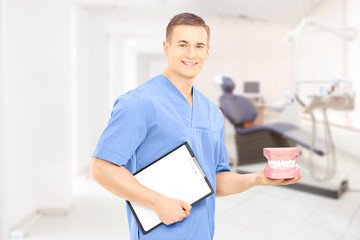 Male dentist surgeon holding dentures at his workplace