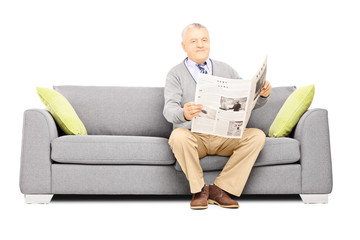 Senior gentleman sitting on a modern sofa with newspaper
