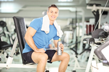 Smiling man on a bench drinking water after exercise in gym
