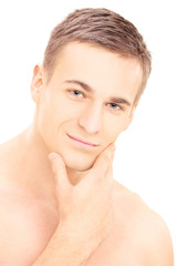 Smiling young shirtless man posing after shaving