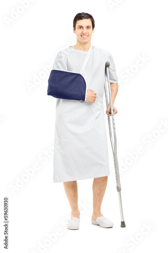 Male patient in hospital gown with broken arm holding a crutch