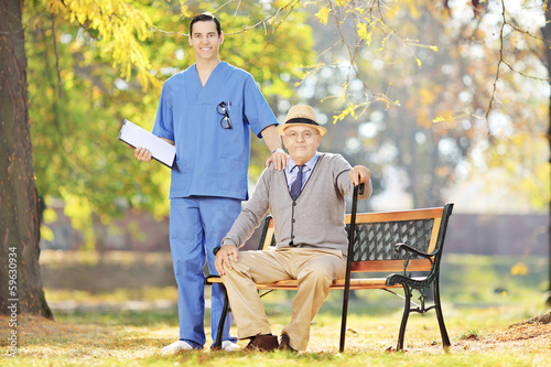 Healthcare professional standing next to a senior man in a park