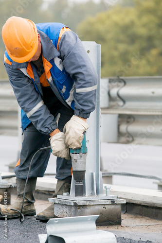 Industrial worker tightening bolts at construction site