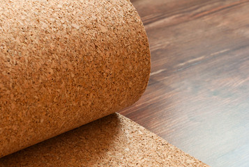 Roll of cork lies on a brown floor